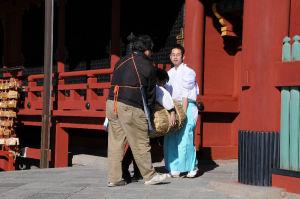 神職が3人がかりで米俵を運んでいます