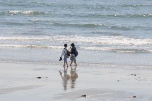 海岸を裸足で散歩する女性