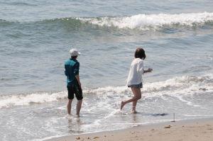 波打ち際で遊ぶカップル