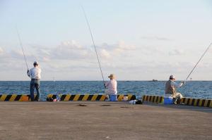 釣りをしている人の先には「裕次郎灯台」