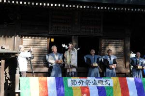 宮司さんが弓を引いています