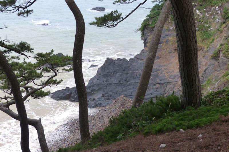 荒々しい岩が海岸から高い崖へ