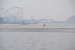 ホバーリングするヘリの風で水面が波立ち